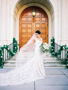 beautiful and classically elegant bride in all lace gown pauses in front of the historic church doors holding her loose and organic bridal bouquet of all white flowers and greenery. the stair rails are dressed with lush greenery garlands with white roses. Used Wedding Dresses, Designer Wedding Dresses, Wedding Gowns, Wedding Picture Poses, Wedding Pics, Allure Bridal, Bridal Beauty, Orlando Wedding Photographer, Elegant Bride