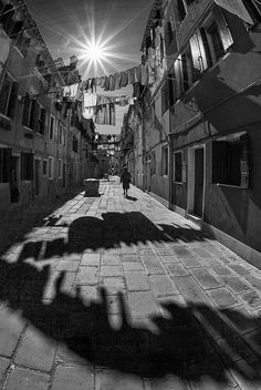 street photography  I found this photograph to be extremely successful in the black and white method that it was shot in. The shadows add contrast and the perspective shot draws the eye down the alley as though one were actually walking down the street.
