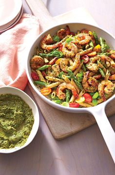 Spinach Pesto Pasta with Shrimp | Pesto is a great big-batch sauce for using up a mix of herbs and greens, but it tends to go army-green if made ahead. We quickly blanch spinach and basil to preserve the color without diluting flavor, then bump up the green with fresh parsley. A little chopped tomato adds moisture and mild acidity. Be sure to press the plastic wrap directly on the surface of the pesto to keep it from browning. A simple shrimp and asparagus pasta toss lets the pesto shine…