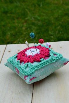 Speldenkussentje, een leuk gehaakt granny-patroon is genaaid op een kussentje van een vrolijk stofje. In de kleuren wit, roze en mintgroen.