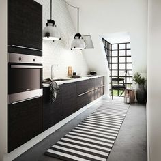 Another kitchen from HTH that's built under a sharply slanted ceiling with black and white details that create a striking contrast in the relatively small, narrow space.
