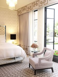 Chic bedroom design with gray cornice board with gold Greek key ribbon trim, gray window panels curtains with gold Greek key ribbon trim, mirrored tufted bed, lilac velvet chair, mirrored round accent table and gray rug.