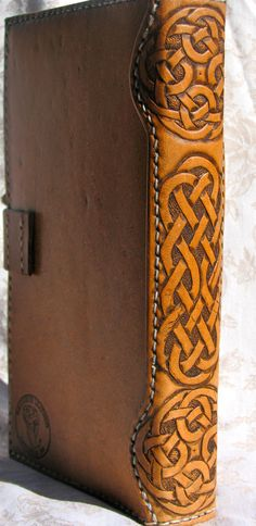 hand tooled celtic knot work on the binding of a leather journal cover.