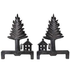 """Pine Tree and Shaker Style House andirons circa 1920s  Cast and hand finished iron with a natural black/brown patina.  This pair of extraordinary andirons are a unique expression of American Folk Art at it's best. The tall tree form resembles a towering carved wood version of a pine tree in 1 1/2"""" thick cast iron and the Shaker Style house with a classic pitched roof and chimney has four """"windows"""" that light up when the fire is roaring from behind."""