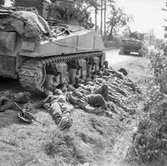 Troops of British King's Shropshire Light Infantry regiment resting next to a Sherman tank of British 3rd Royal Tank Regiment France 15 August 1944.: