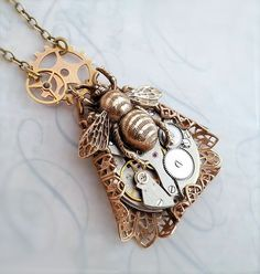 Steampunk necklace features a Victorian style bee. This beautiful steampunk bee is set on a steel metal vintage watch movement with authentic ruby jewels. Please note: I use genuine antique watch mechanisms, you will not receive the exact one pictured...You will receive your own unique 1 of a kind original steampunk necklace designed as in the photo with an equally beautiful watch mechanism. Suspends from a thick and beautiful solid brass vintage chain. I used Vintage tooled brass filigree…