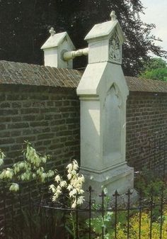 Man and wife, unable to be buried side by side in the same cemetery, so their headstones hold hands over the wall.