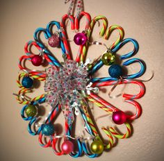 Made with 22 Jelly-Belly candy canes, hot glue, silver star, small ornaments, silver ribbon, and a pretty bow made out of polka-dot ribbon!  Fun project.  I also used a cardboard circle in the back of the center to give it more stability.