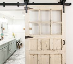Stunning home tour - they turned a plain Jane ranch into farmhouse perfection! Love this chippy old sliding barn wood door in the bathroom eclecticallyvintage.com