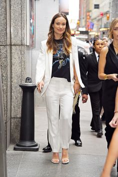 Looking to a T-shirt yet again, the star wears her graphic style with a sharp white cape, loose-fitting trousers, and white sandals. It's like the perfect combo of runway and rock 'n' roll.   - HarpersBAZAAR.com