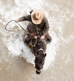 Cool pic! Cowboy on horse in the water from aerial view.