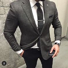 grey suit white shirt and black patterned tie!