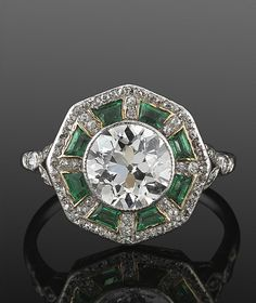 Old European Cut Diamond and Emerald Ring, circa 1915. An old European cut diamond weighing approximately 2.10 carats is surrounded by calibre emeralds and a total of approximately 1 carat of single cut diamonds set in platinum.