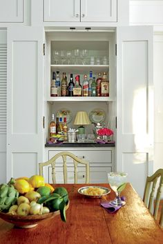 Modern eyesore appliances—refrigerator, dishwasher, laundry machines—and even a fully stocked bar are hidden behind paneled doors, allowing the home to feel both older and uncluttered. #homedecor #southernliving