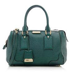 This classic Burberry small tote is made from grained calf leather in the dark cyan color with gold-tone hardware. Details include two rolled handles, a zip closure, and fully lined interior with two open pockets and one zippered pocket. Carry this style on the forearm or over the shoulder with a detachable strap.