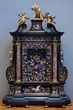 """Medici Night Clock, Pietre Dure, Giovanni Battista Foggini, Florence, 1704-1705, ebony, gilt bronze, semiprecious stones. Giovanni Foggini was artistic director for the Grand Duke of Tuscany in Florence from 1694-1725. Table clocks were fashionable in ebony cases with pietre dure reliefs. At the crest, a miniature of Pietro Tacca's bronze of ca.1630 called """"Il Porcellino"""" (the piglet), a most famous symbol of Florence."""