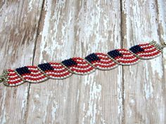 The American flag bracelet is made using opaque white, opaque dark red luster, opaque royal blue luster and permanent galvanized silver seed beads. The beads are stitched together using peyote stitch. In order to make the flags appear to be waving, I manipulate the peyote stitch with additional thread. What a beautiful way to show your support for the great American Flag!  The Spirit of America bracelet is custom made to fit your wrist size. If your size is not listed, please feel free to…