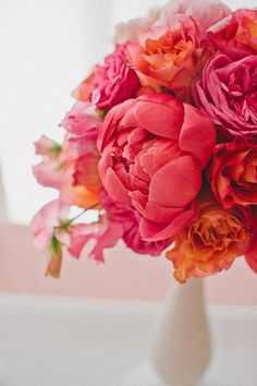 A bright pink and coral wedding centerpiece with peonies.