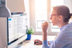 Female business person reading email on computer screen at work