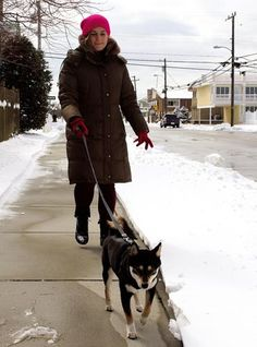 Kira Moyer of Wildwood Crest is bundled up as she takes her Shiba Inu named Becka for a snowy walk.