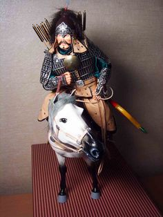 Paper mache life-like rendition of Genghis Khan on horseback, made with close attention to details. Facial expression looks very real. Weapons made of plastic and metal. All items that are supposed to be of leather (i.e. saddle, pouch, side face cover, reins, etc) are made of leather (of which Mongolia has a lot). Bought in Ulaan Baatar.