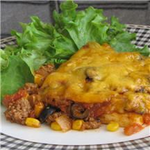 Tamale Pie - This hearty Tex-Mex ground beef pie has an easy cornmeal crust layered with a tasty chili-style meat filling and topped with cheddar cheese.