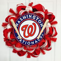 Washington Nationals MLB fans support your team by sporting this barn red baseball wreath! It encompasses all things baseball in a beautiful way and features a 12 Washington Nationals embossed metal circular sign, four solid cork baseballs, two Louisville slugger mini baseball bats, and complete with baseball stitch ribbon.  Only ships within the United States, excluding HI & AK.  **To preserve quality of wreath, we recommend that you keep wreaths under a covered area or bring wreaths ind...