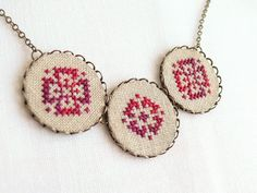 Cross stitch necklace with three ombre red ornament in bronze. $30.00, via Etsy.