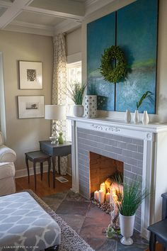 Log and candles in the fireplace with river rock - faux fireplace? Also love that painting with wreath.