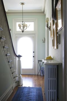 White trim compliments pale green walls of an entry