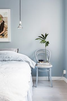 Serene blue bedroom with a chair doubling as a nightstand and hanging pendant light