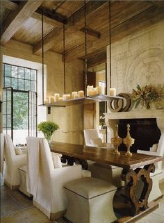 Mediterranean Dining Room with sandstone floors, High ceiling, French doors, Transom window, Chandelier, Exposed beam