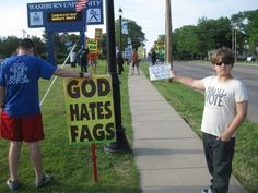 """The boy's sign says, """"God hates no one."""""""
