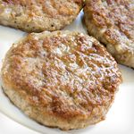 In a skillet over medium-high heat, brown the sausage patties in 1 tsp oil.   Place avocado then cheddar cheese substitute&amp