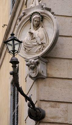 https://flic.kr/p/bV2wGR | Rom, Via dei Banchi Vecchi/Piazza dell'Orologio, Madonna (Virgin Mary) | In Rom gibt es Hunderte von Strassentabernakeln, die alle liebevoll als Madonnelle (kleine Madonnen) bezeichnet werden und zwar unabhängig von der dargestellten Figur. Neben dem frommen und schmückenden Zweck hatten sie auch eine Funktion, denn in Zeiten als es noch keine Strassenbeleuchtung gab, wiesen ihre Andachtslämpchen nächtlichen Passanten den Weg.  .