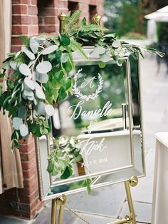 Elegant mirror framed wedding sign dripping with eucalyptus: http://www.stylemepretty.com/2016/09/25/handwritten-notes-served-as-escort-cards-for-their-300-guests/ Photography: Michelle Lange - http://www.loveandbemarried.com/