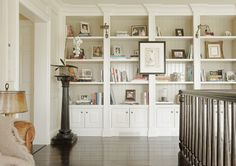 Foor to ceiling bookshelves with cabinets below