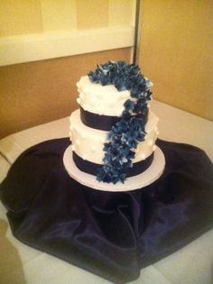 Navy blue hyacinth and forget-me-not sugar flowers form the topper and arch down the front.