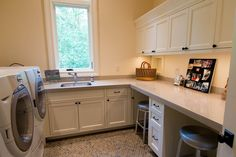 Clean, simple and organized laundry room design with desk seating. From 1 of 17 projects by Riverland Homes.