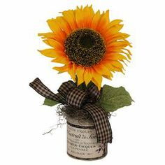 "Artful on its own or anchoring an organic-chic vignette, this faux sunflower arrangement is nestled in a charming pot adorned with French typography.    Product: Faux floral arrangementConstruction Material: Silk, plastic, glass and cottonColor: Orange, yellow, black and greenFeatures: Includes faux sunflowersCheckered ribbon accentFrench typography motifSuitable for indoor use only  Dimensions: 14"" x 9"" W x 8"" D"