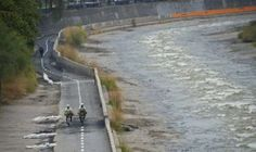 Cyclists ride along a bike path on the banks of the Mapocho River in Santiago on April 1, 2016