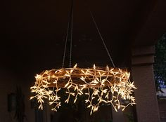DIY Icicle Chandelier. By The Project Table. Using Grapevine wreath, icicle lights, zipties and chains.