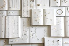 wow! plain white book pages make for a unique jewelry display backdrop.