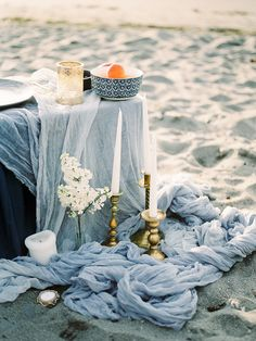 Intimate Seattle Beach Wedding | Golden Gardens Beach served as the perfect setting for a romantic beach wedding reception. The long textured linens of this blue and gray tablescape contrasted beautifully with the light neutrals of the surrounding PNW landscape. Modern decor was mixed in with vintage elements such as the ornate gold candle holders and colored glass drinking goblets. Fresh flower arrangements by Leah Erickson Floral softened up the sweetheart table, creating a lush look that…