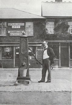 The town pump in Market Square, Rochford. c1920 – the local newsagent waits for his pail to fill.