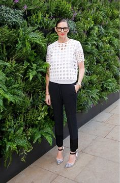 Jenna Lyons poses in a white cutout top, black trousers, and ankle strap heels.