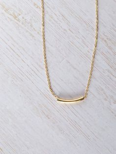 Delicate curved gold bar necklace