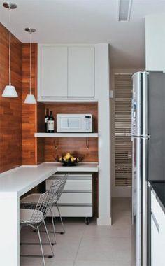 """A sala não comportava uma mesa de jantar, mas a bancada de 2,10 x 0,50 m na copa (MDF revestido com melamina branca) resolveu o problema. """"Para reforçar a integração, usamos a mesma forração de madeira de peroba-do-campo da sala de estar"""", aponta a arquiteta."""