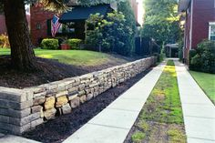 Low stone wall provides a handsome, yet unobtrusive border. www.oldworldtrades.com