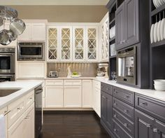Traditinal Kitchen: White + grey cabinets with dark wood floors and stainless steel appliances  OmegaCabinetry.com